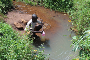 A student gets drinking water from a polluted water source.